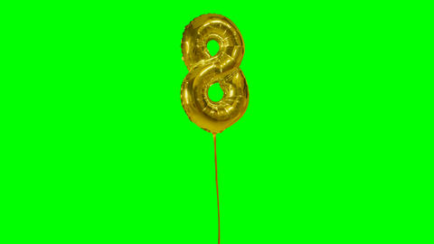 Number 8 eight years birthday anniversary golden balloon floating on green Live Action