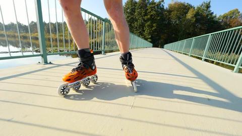 Man legs skating on light asphalt path on lake bridge. Outdoor inline skating. ビデオ