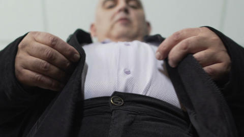 Fat man trying to fasten a button on his jacket, extra weight, bottom view Footage