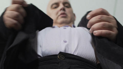 Base view of plump man in classic suit fastening a button on his jacket, closeup Footage
