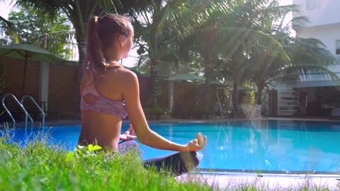 sun rays light girl relaxing in pose Lotus by pool side view Footage