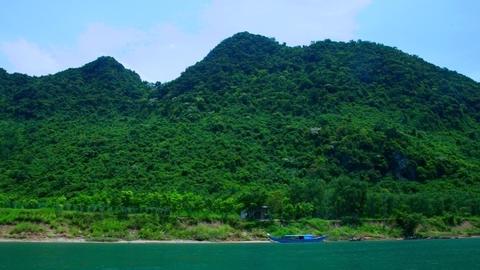 floating past forestry hills on river bank under blue sky Footage