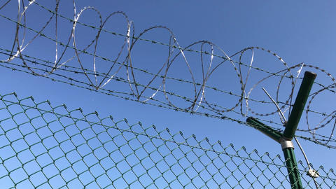 Barbed wire on net fence under blue sky Footage