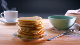 Tasty cooked pancakes on the table with steaming hot drink and honey on a table Footage