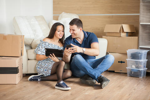Young beautiful couple sitting on floor in their new flat フォト