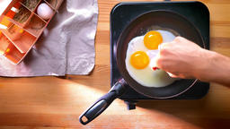 Top shot, adding salt to almost cooked eggs on pan at home, healthy eating ビデオ