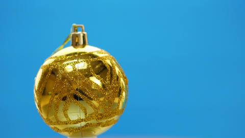 Decorated yellow Christmas balls spinning on blue background Archivo