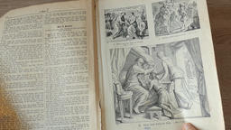 Hands are turning pages of an old, german language, illustrated bible Footage