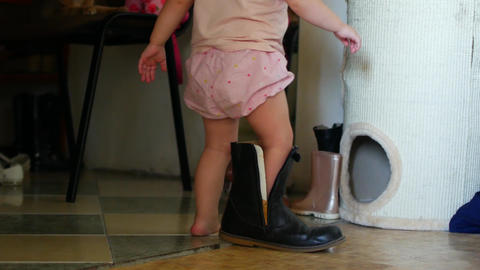 A little girl in her mother's shoes by the mirror. A child in adult shoes Footage