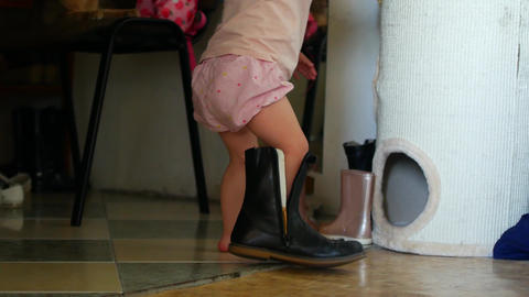A little girl in her mother's shoes by the mirror. A... Stock Video Footage