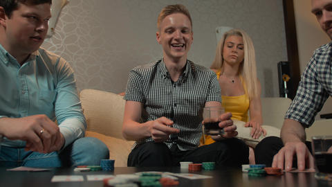 We have a winner. Young People playing poker in home Live Action