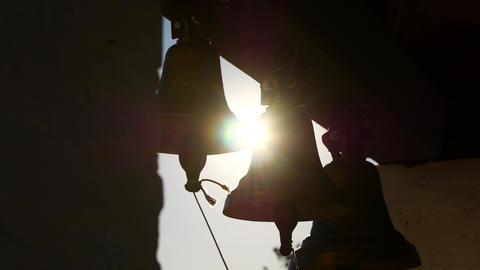 Silhouette of bells at sunset. Sun rays ビデオ