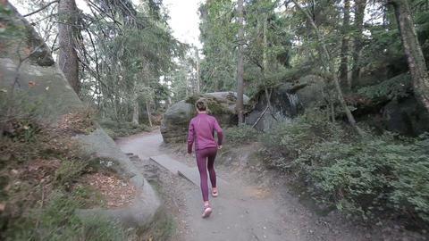 Young woman runs through a tourist pass among rocks and stones. Tracking shot ビデオ