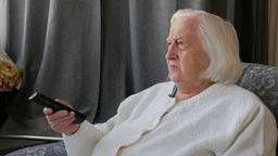 Old, senior woman is sitting in an armchair and watching TV at home. 1 Footage