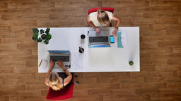 Top down shot, two working blondes at wooden office checking paper graphs with Archivo