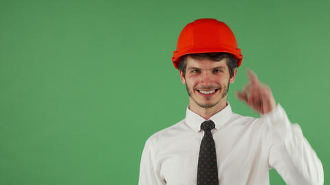 Cheerful handsome male engineer wearing hardhat winking to the camera Archivo