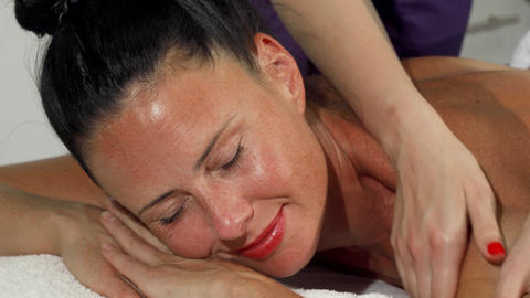 Happy beautiful woman smiling to the camera while getting massage Live Action