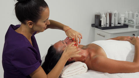 Therapist performing facial massage for mature woman Live Action