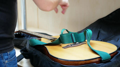 Guitar player folds acoustic guitar in a black case after concert ビデオ