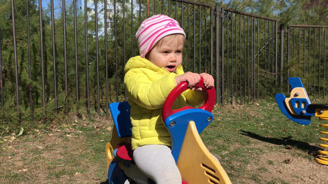 Toddler swinging on rides with joy, child on playground Footage