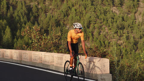 A man on a sports road bike rides on the road located high in the mountains Footage