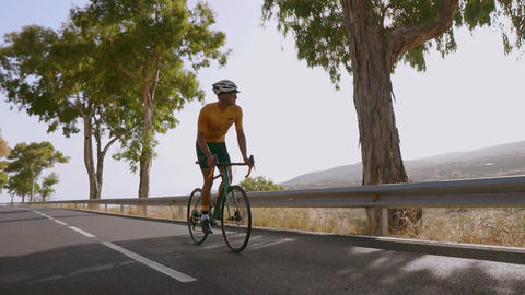 Man cycling on road bike outdoor exercise on an empty road in the morning Live Action