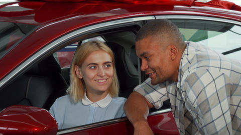 Cheerful young couple buying new automobile Live Action