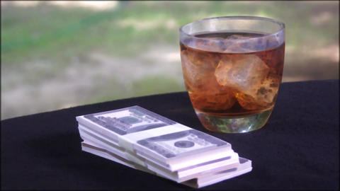 Glass of whisky and dollar bills on the table Archivo