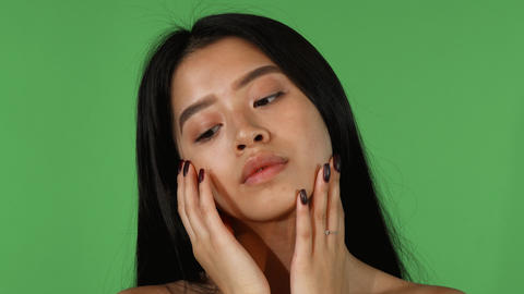 Shot of a gorgeous Asian woman touching her face Live Action