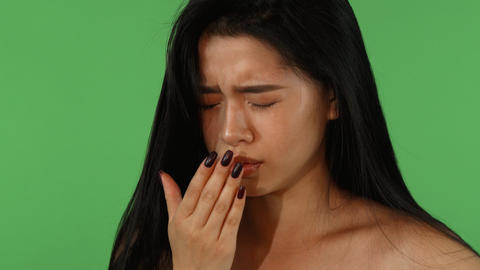 Beautiful Asian woman feeling sick and coughing on green chromakey Footage