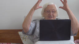 Funny old lady with a laptop computer. Online gambling Live Action