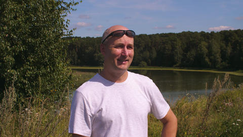 Portrait adult man breathing fresh air in summer forest on lake background Live Action