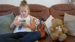 Young girl is playing game on a smartphone Footage