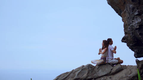Man and woman sitting on top of a mountain on a rock back to back meditate and Live Action