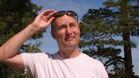 Portrait adult man wearing sunglasses at sunny summer day in green forest Archivo