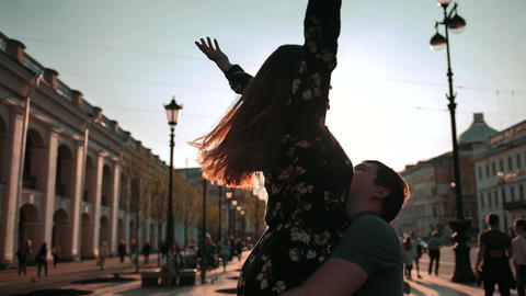 Young couple, male and female, dancing at sunset street, they turning and ビデオ