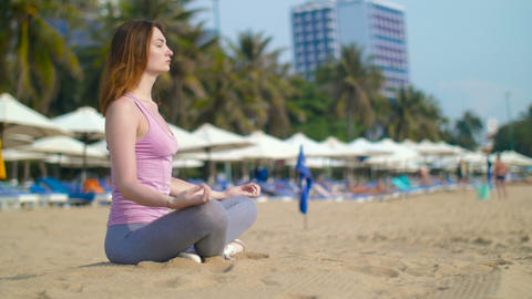 Girl meditating on the beach Live Action