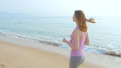 Woman runner running on beach road Footage
