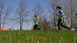 Athletes Running Through City Streets On Background Of Blue Sky And Green Grass stock footage