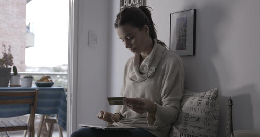 Woman with credit card writing on tablet Live Action
