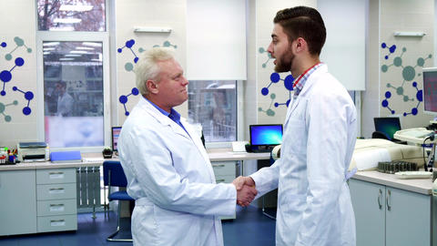 Two male scientists greet each other at the laboratory ビデオ