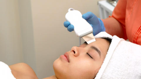 Beauty specialist makes ultrasonic peeling for female client's face Live Action