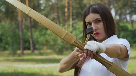Female archer aiming her bow on target Live Action