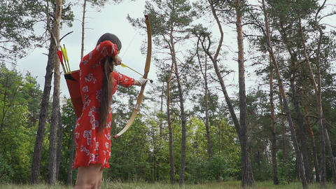 Girl is trying to hit an arrow in a tree Live Action