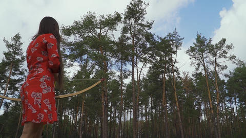 Girl in red dress practice in shooting in forest Live Action