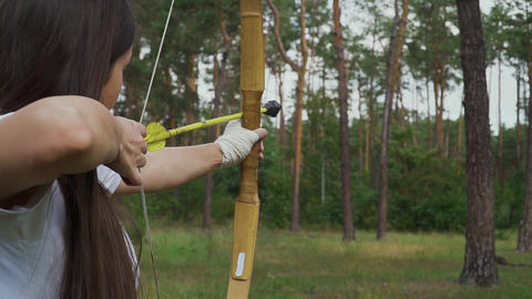 Young girl draving arrow and shooting target Live Action