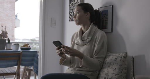 Woman browsing and texting on her phone by the window - 4K Stock Video Footage