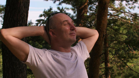 Happy bald man in white t-shirt relaxing in summer forest or park Footage