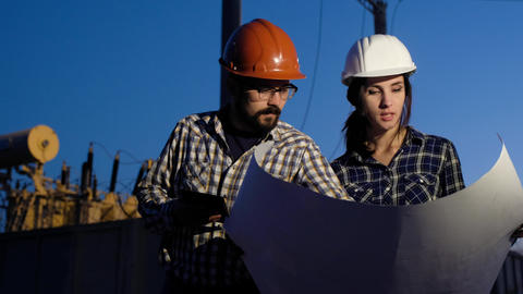 Woman in the male profession. Two engineers make calculations on a big piece of Live Action