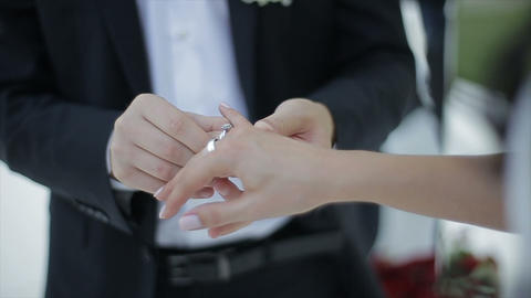 Groom puts the wedding ring on Bride's finger. Marriage, hands with rings. The Footage